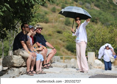 EPHESUS, TURKEY - June, 06, 2014: A group of tourists gather around a tour guide in the celsus library area of Ephesus in order to hear the guide tell them about the site.