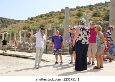 Ephesus, Turkey - June, 26, 2014: A group of tourists gather around a tour guide in the celsus library area of Ephesus in order to hear the guide tell them about the site.