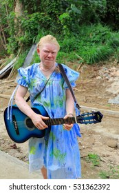 Epi island, Vanuatu-October 5, 2014: Albino girl with blue guitar makes the pedestrian route between Lamen Bay and Nikaura villages from the E.shore to the W.across the island. Shefa province-Vanuatu.