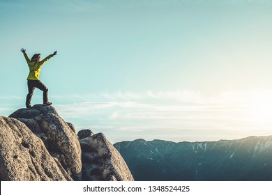 Epic adventure of brave and ambitious hiker trekking activity on wild cliff, pose with panoramic nature mountain landscape. Winner motivation and power discovery travel concept.