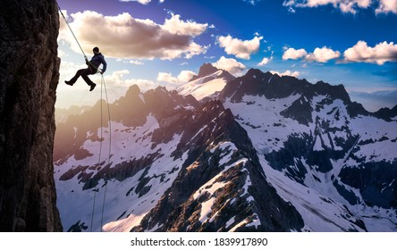 Epic Adventurous Extreme Sport Composite of Rock Climbing Man Rappelling from a Cliff. Mountain Landscape Background from British Columbia, Canada. Concept: Explore, Hike, Adventure, Lifestyle