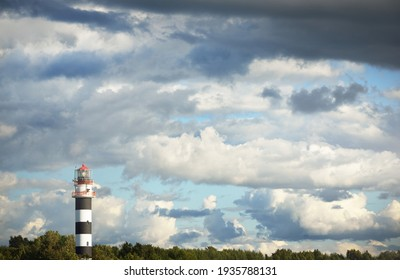 Epic cloudscape. Lighthouse against dramatic sky with ornamental cumulus clouds before the rain. Fickle weather. Baltic sea. Texture, background, wallpaper, graphic resources, design, copy space