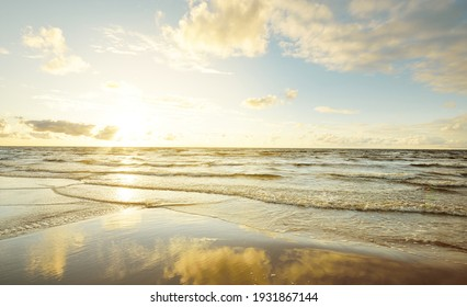 Epic colorful glowing golden sunset clouds above the sea after a thunderstorm. Dramatic sky. Waves and water splashes texture. Idyllic seascape. Concept image, long exposure. Picturesque scenery