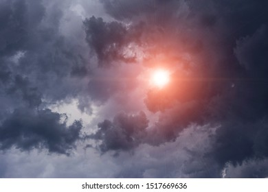Epic cumulus storm dark grey clouds background with sun and sunlight