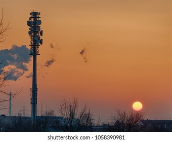 Epic dusk scene with a huge radio tower silhouette in the glowing yellow sunset of a summer evening, HDR version