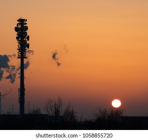 Epic dusk scene with a huge radio tower silhouette in the glowing yellow sunset of a summer evening