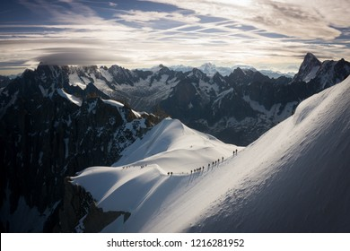 Epic landscape with line of mountaineers on decent from Aiguille du Midi cable car station in Mont Blanc, Chamonix (France) in summer, getting ready for adventure. Snow, glacier, mountains.