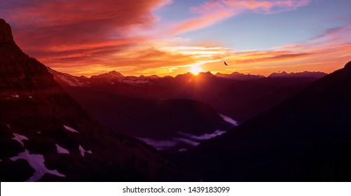 Epic Mountain Sunset Over Glacier National Park High Altitude Range of Peaks With Eagle Flying In Distance