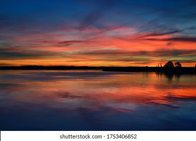 Epic red sunset sky above the lake and forest in autumn. Dramatic cloudscape. Symmetry reflections on the water, natural mirror. Idyllic rural scene. Gauja national park, Sigulda, Latvia