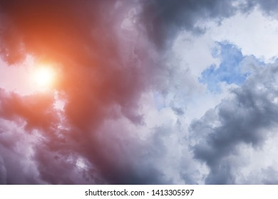 Epic scenic storm dark clouds background with sun and orange sunlight. Darkness and light