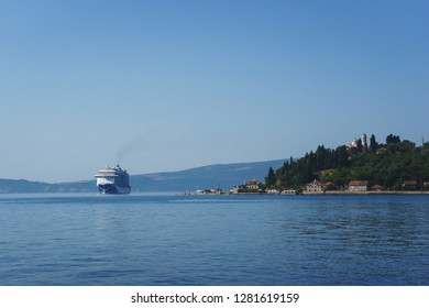 Epic seascape: a huge cruise liner in a narrow strait along the coast with a small town. White passenger liner in the bay. Montenegro, Boka Kotorska bay on a hot summer day. Travel to Montenegro.