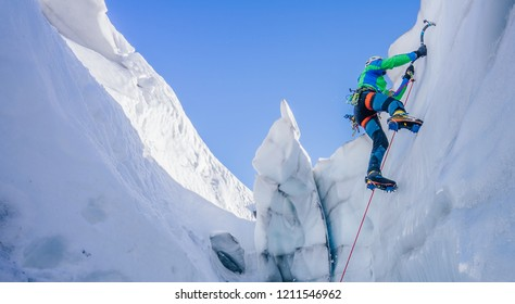 Epic shot of an ice climber climbing on a wall of ice. Mountaineer and climber on an adventure extreme ascent with ice axe and crampons. Alpine extreme climbing on a serac or creavasse.