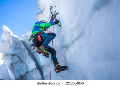 Epic shot of an ice climber climbing on a wall of ice. Mountaineer, climber or alpinist on an adventure extreme ascent with ice axe and crampons. Alpine extreme climbing on a serac or crevasse.
