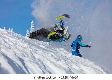 epic snowmobile fall. sports snowmobiles in the mountains. bright skidoo motorbike and suit without brands. Winter fun, snowmobilers sports riding. high resolution photos