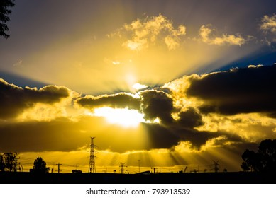 A epic sun setting behind clouds above powerlines and pylons in Melbourne Australia