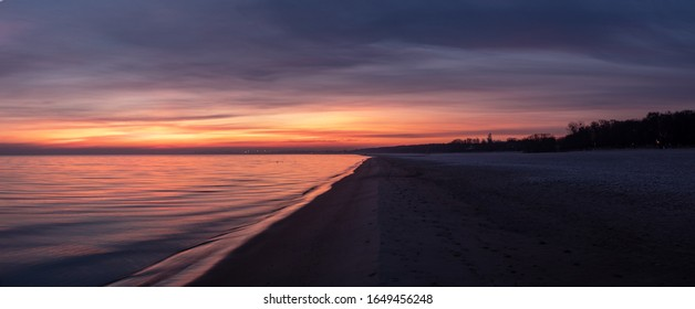 Epic sunrise in the cold winter morning at the beach. Colorful sky with multiple various colors with dark and moody land. Wide angle photography panorama style.