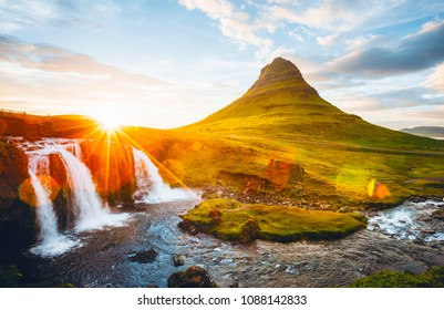 An epic sunset with Kirkjufellsfoss waterfall. Location Iceland, Europe. Scenic image of tourist attraction. Travel destination of most popularly photographed place. Discover the beauty of earth.