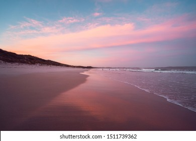 Epic sunset over Cosy Corner Beach, Albany, Western Australia. Incredible pink and blue sky above the beach with waves crashing on the shore and people playing with their children in the distance.