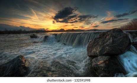 Epic sunset with small river waterfall in foreground