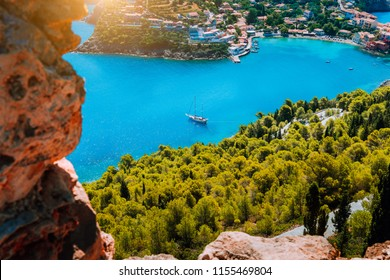 Epic view to blue bay of Assos village Kefalonia in warm morning sun light. White yacht at anchor in calm beautiful lagoon surrounded by pine and cypress trees. Greece