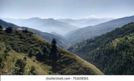 Epic view of Fagu Valley, Himachal Pradesh. The mountains are beautifully arranged in layers and covered with mist.