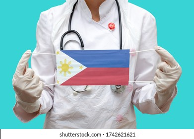 Epidemic in Philippines. Young woman doctor in a medical coat (suit) and gloves holds a medical mask with the print of the flag of Philippines on a blue background isolated.