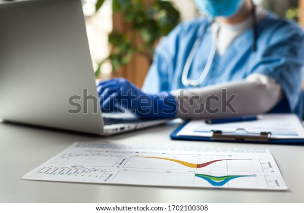 Epidemiologist doctor working on laptop computer,analyzing graphs & charts,COVID-19 Coronavirus global pandemic crisis outbreak,mortality rate death toll statistics,research & data comparison