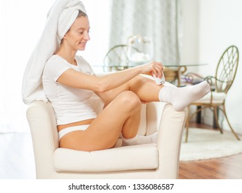Epilation. Woman epilates her leg with an electric epilator device at home.