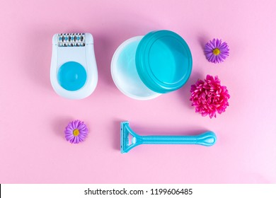 Epilator, cream, women's shaving razor and flowers on a pink background. Depilatory. Removal of unwanted hair. Spa and Female treatments. Epilation concept