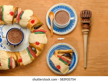 Epiphany cake, Kings cake, Roscon de reyes or Rosca de reyes on wooden table with hot chocolate cup made with cinnamon and beaten with wooden utensil called molinillo