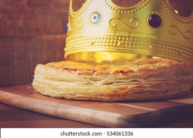 Epiphany Twelfth Night Cake, Almond Galette des Rois, Cake of the Kings, with crown on dark wood rustic background, with applied retro vintage style filters.