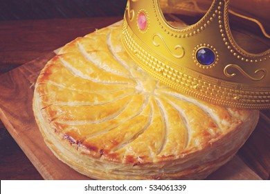 Epiphany Twelfth Night Cake, Almond Galette des Rois, Cake of the Kings, on dark wood rustic background, with applied retro vintage style filters.