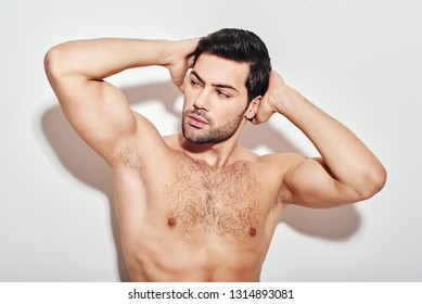 Epitome of masculinity. Handsome man shows off his perfect body looking away, isolated over white background