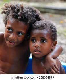 EPI,VANUATU-OCTOBER 4, 2014: Brothers share a bath with a laugh in front of the photographer on October 4, in Lamen Bay-Vanuatu.