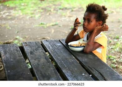EPI,VANUATU-OCTOBER 4, 2014: Girl eats his daily food on a wooden table on October 4, in Lamen Bay-Vanuatu.