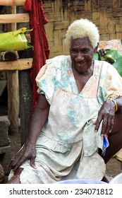 EPI,VANUATU-OCTOBER 5, 2014:Grandmather makes coconut milk at the entrance of their hut on October 5, in Nikaura-Vanuatu.