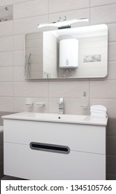 epmty minimalistic interior background, bathroom of modern apartment, closeup of mirror, tap and basin in light colors, nobody, with copy space, vertical