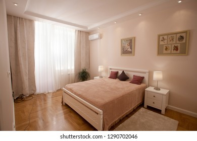 epmty minimalistic interior background, bedroom of modern apartment with big mirrors, double bed, lights on, nobody, with copy space, horizontal