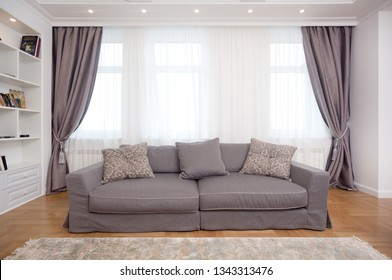 epmty minimalistic interior background, living room of modern apartment with big windows and sofa, daylight, front view, with copy space, horizontal
