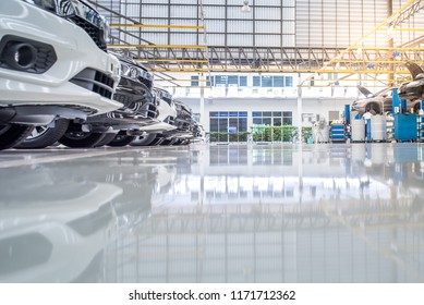 Epoxy floor in a car repair station There is an electric car lift for car repair in industrial plants with epoxy floors.