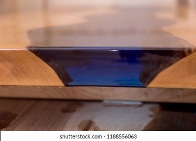 Epoxy resin in cracked walnut massif. Artistic processing of wood. furniture loft. modern furnishings.table-tops