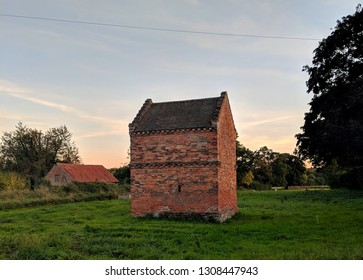 EPPERSTONE, ENGLAND - FEBRUARY 2, 2019:  A historic Late C17, Red brick,  ashlar,  plain tile roof dovecote (also known as a pigeongcote) and barn in Epperstone, Nottinghamshire, UK
