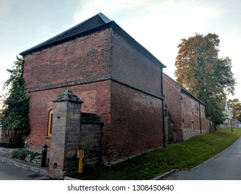 EPPERSTONE, ENGLAND - FEBRUARY 2, 2019:  A historic C17, Red brick, ashlar,  pyramidal plain tile roof dovecote (also known as a pigeongcote) and barn in Epperstone, Nottinghamshire, UK