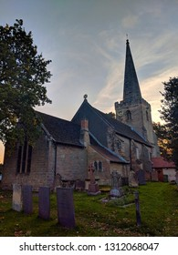 EPPERSTONE, ENGLAND - SEPTEMBER, ‎2018: Church, spire and graveyard against the early evening sky at Holy Cross Church, Epperstone, Nottinghamshire, UK