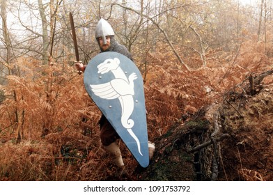 Epping Forest Essex UK 1995. An unidentified reenactor of the Dark Ages stands in woodland sword and shield in hand dressed in the period armour of a Norman Knight 1066.