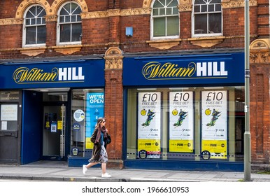 Epsom Surrey London UK, May 02 2021, Single Woman Walking Past A High Street Branch Of William Hill Betting Shop