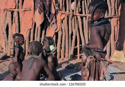 EPUPA, KAOKOLAND/NAMIBIA - OCTOBER 16: Himba youngsters talk and drink on October 16, 2010 near Epupa, Namibia. Names-Ages (l.-r.): Umuniangwe-4,Mukakamunwe-3,Menjamwapi-11,Twakoseka-10,Uvaserwa-11.