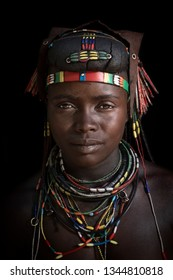 Epupa, Kunene Region, Namibia - November 24, 2017 : A Muhacaona woman poses for a portrait of the finer details of her traditional hair and jewelry. The Muhacaona cross from Angola to Namibia to trade