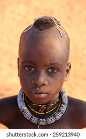 EPUPA, NAMIBIA- MAY 12, 2014: Unidentified Himba child. Himba children show their traditional clothing, jewelry and headdress. The age and social status  can be seen in their hairstyle and jewelry.