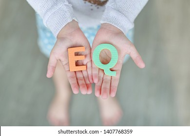EQ (Emotional Quotient) sponge text on child hands. Education and development concept.